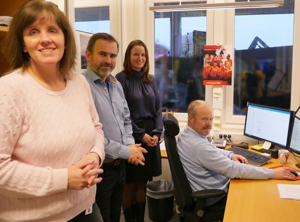 Tone Ballott Runestad, arbeidsgiver Martin Nordbø, koordinator fra hjelpemiddelsentralen Beate van der Meijs og Willy Fotland er samlet inne på kontoret til Fotland.