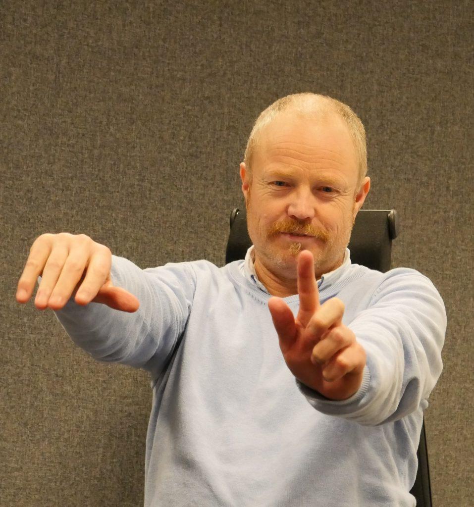 Willy Fotland holder begge hendene rett fram. Når han ser på den ene hånden kan han ikke se den andre.