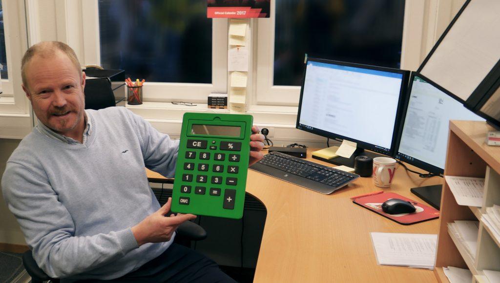 IKKE SÅ ILLE: Willy Fotland ler i det han viser frem en kalkulator han fikk i gave fra kollegene da han begynte i ny stilling. Enn så lenge klarer han seg uten synshjelpemidler i den nye stillingen.