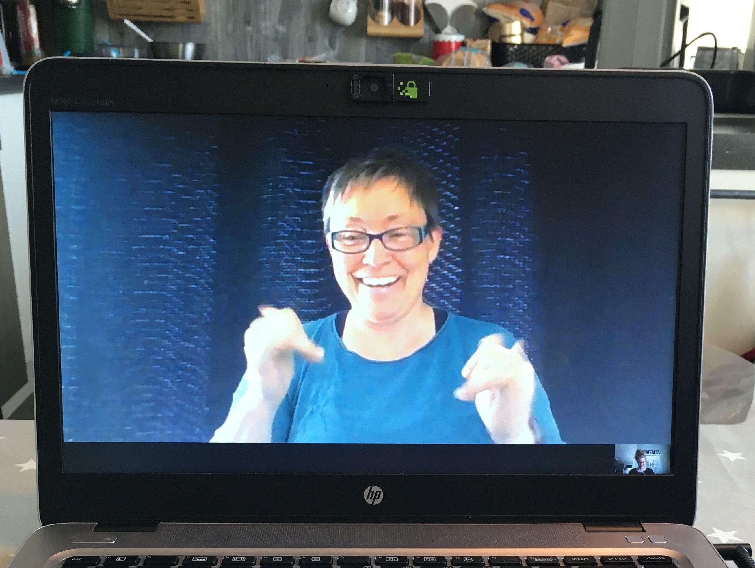 """TOLKER FRA HJEMMEKONTOR: Anne Grete Fandin, tolk for døve, døvblitte og døvblinde, demonstrerer hvordan det fungerer med videotolking. Her sier hun entusiastisk """"JA"""". Foto: Silje Helen S. Rygh"""